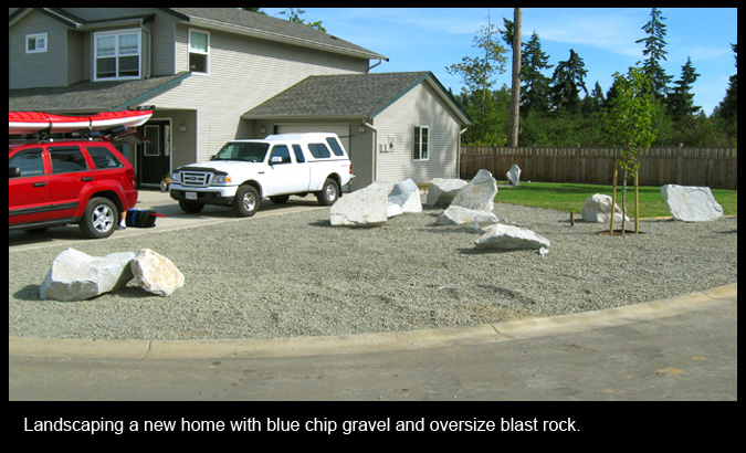 Landscaping a new home with blue chip gravel and oversize blast rock.