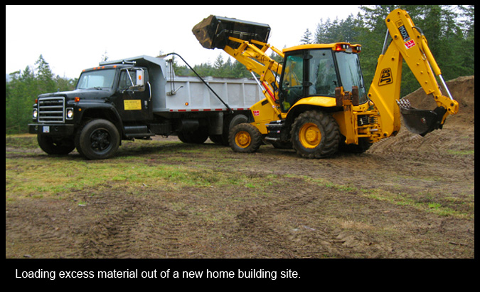 Loading excess material out of a new home building site.